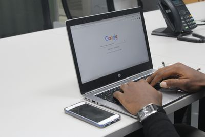 Person on laptop using Google next to mobile and landline phones