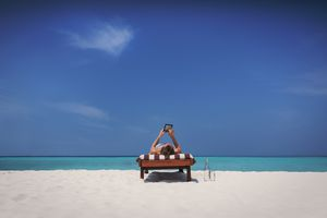 Woman laying on lounge chair and using digital tablet on sunny tropical beach