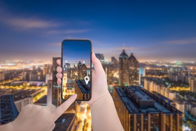 Person using an Android smartphone with city in background
