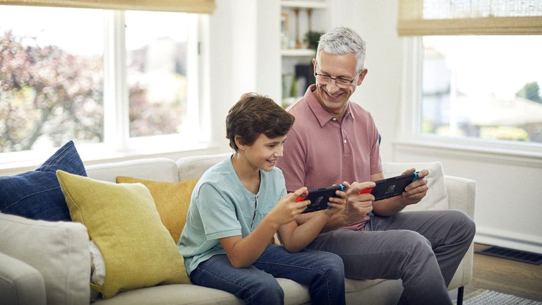 A man and a boy playing on two Nintendo Switch consoles.