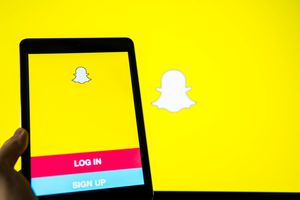 A hand holds a smart device while using SnapChat app