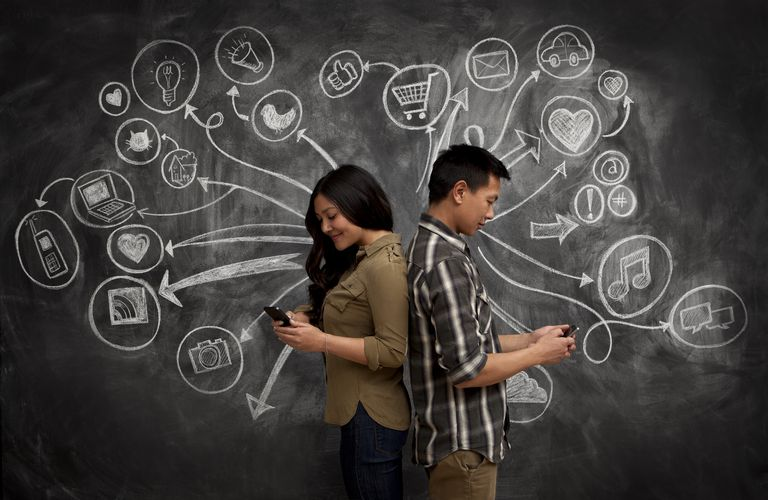 Man and woman texting in front of a large chalkboard