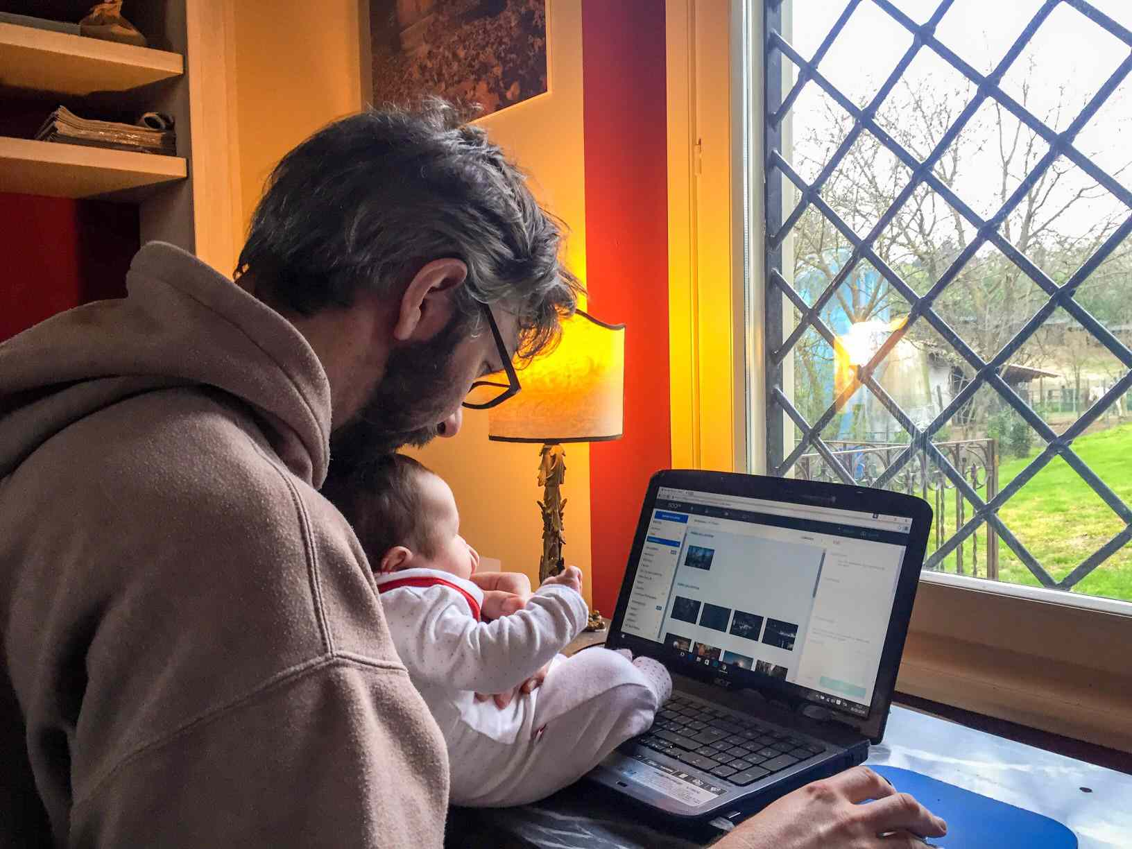 A man working on his laptop at home, holding his baby.