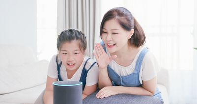 A woman and child speaking to a smart home assistant.