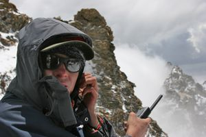 Someone in a snow covered mountain area using a satellite phone.