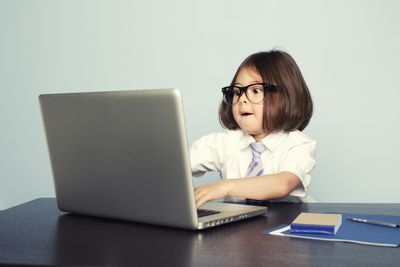 Young Girl Wearing Tie Types on Laptop