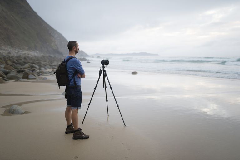 Photographer taking photos on the beach with a tripod