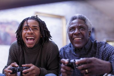 A son and a father playing video games