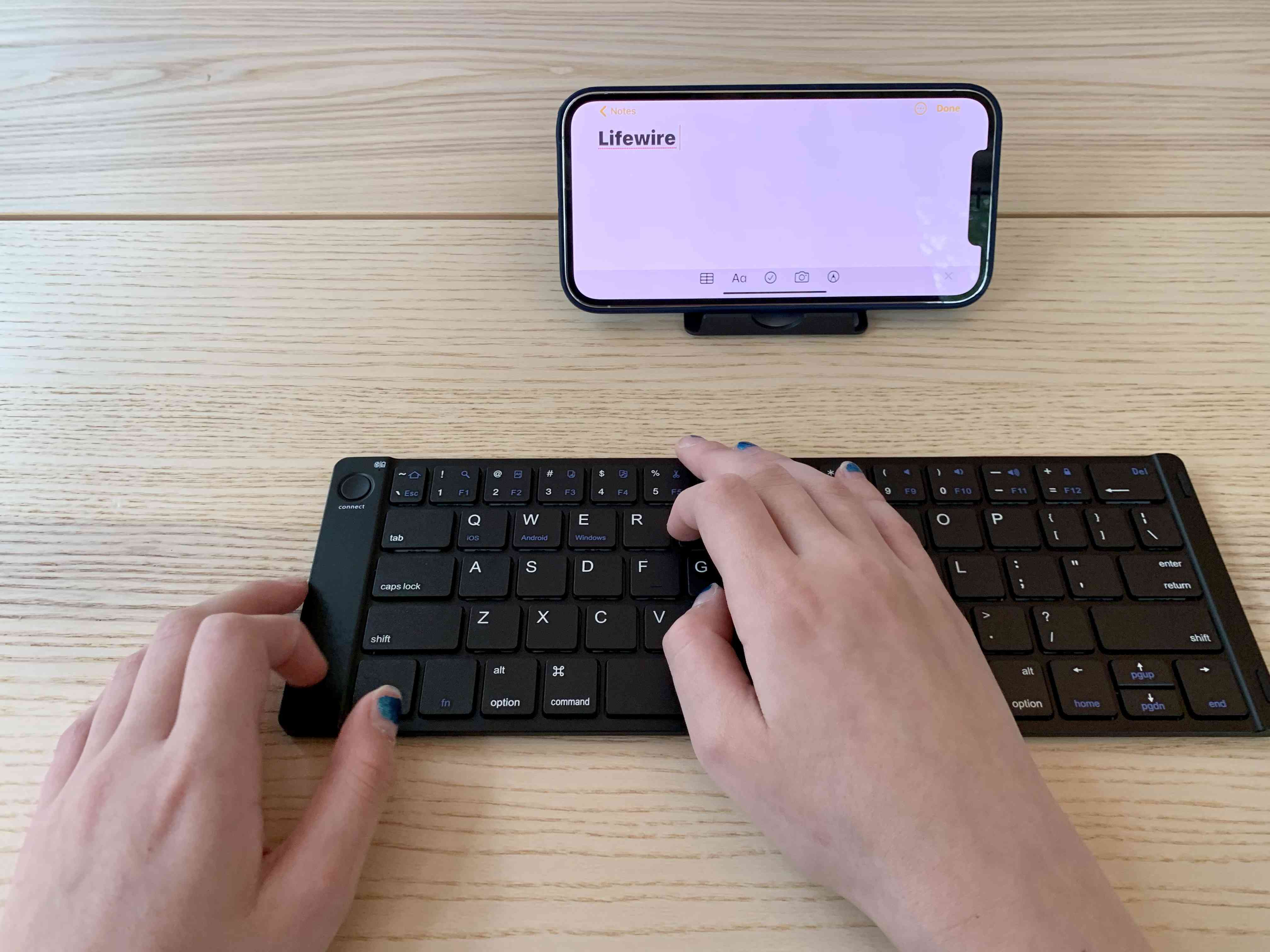 Hands using a Samsers foldable keyboard with an iPhone