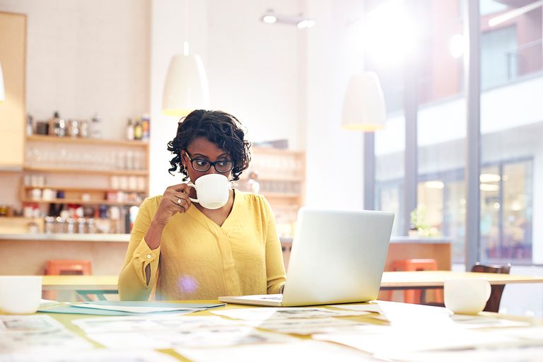 Creative woman working at desk with coffee