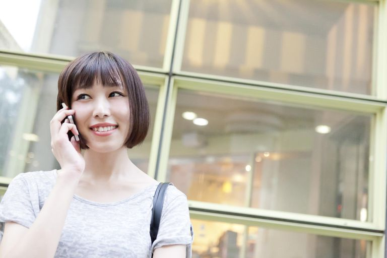 Woman talking on smartphone on street,smiling