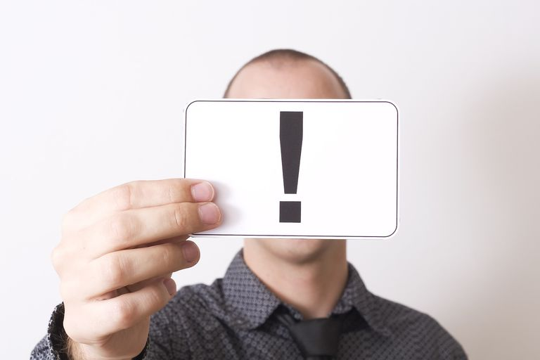 Man holding note of exclamation point in front of face