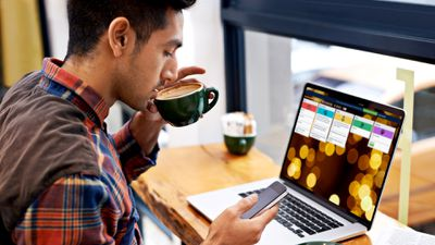 A man drinking coffee while managing Trello tasks on his laptop and smartphone.