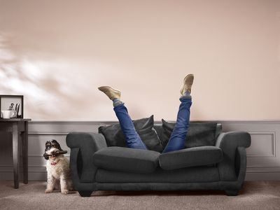 A pair of legs sticking out of a couch