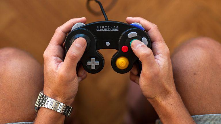 A man holding a Nintendo GameCube controller.
