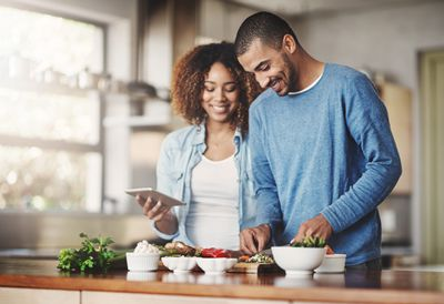 A couple creating a vegetarian meal in the kitchen.