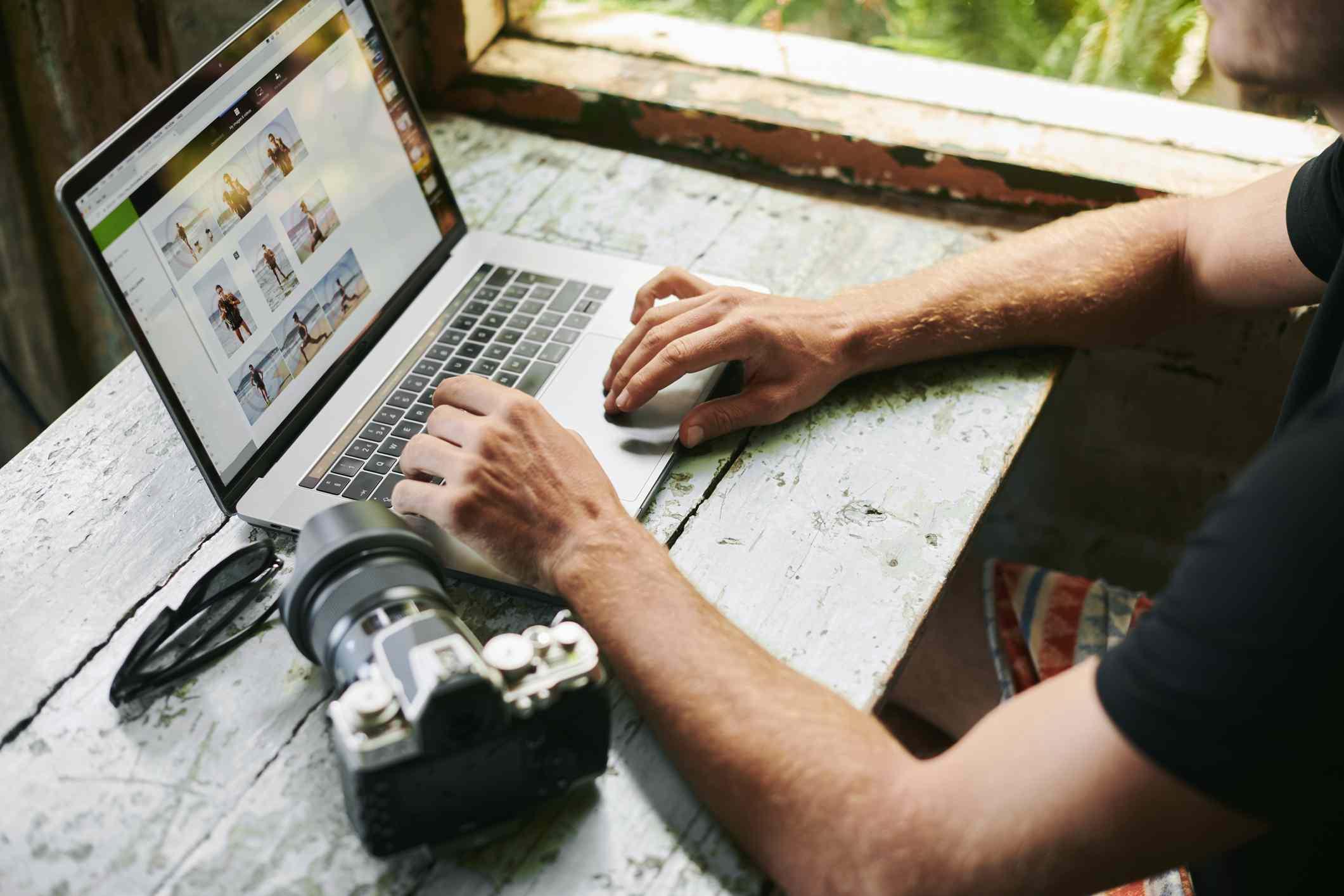 A photographer editing photos on a laptop.