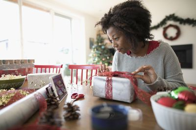 Woman watching video tutorial on digital tablet, wrapping Christmas gift at dining table