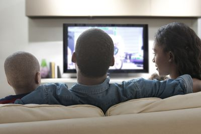 A man, woman, and boy watching TV.