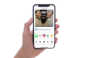 Hand holding an iPhone, video selected to share via AirDrop.