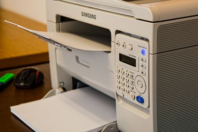 A Samsung printer with paper loaded.
