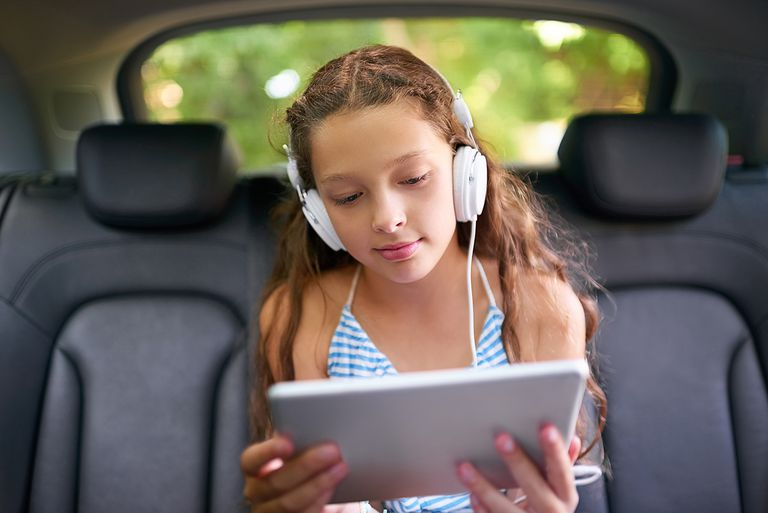 Shot of a young girl sitting in a car wearing headphones and using a digital tablet.