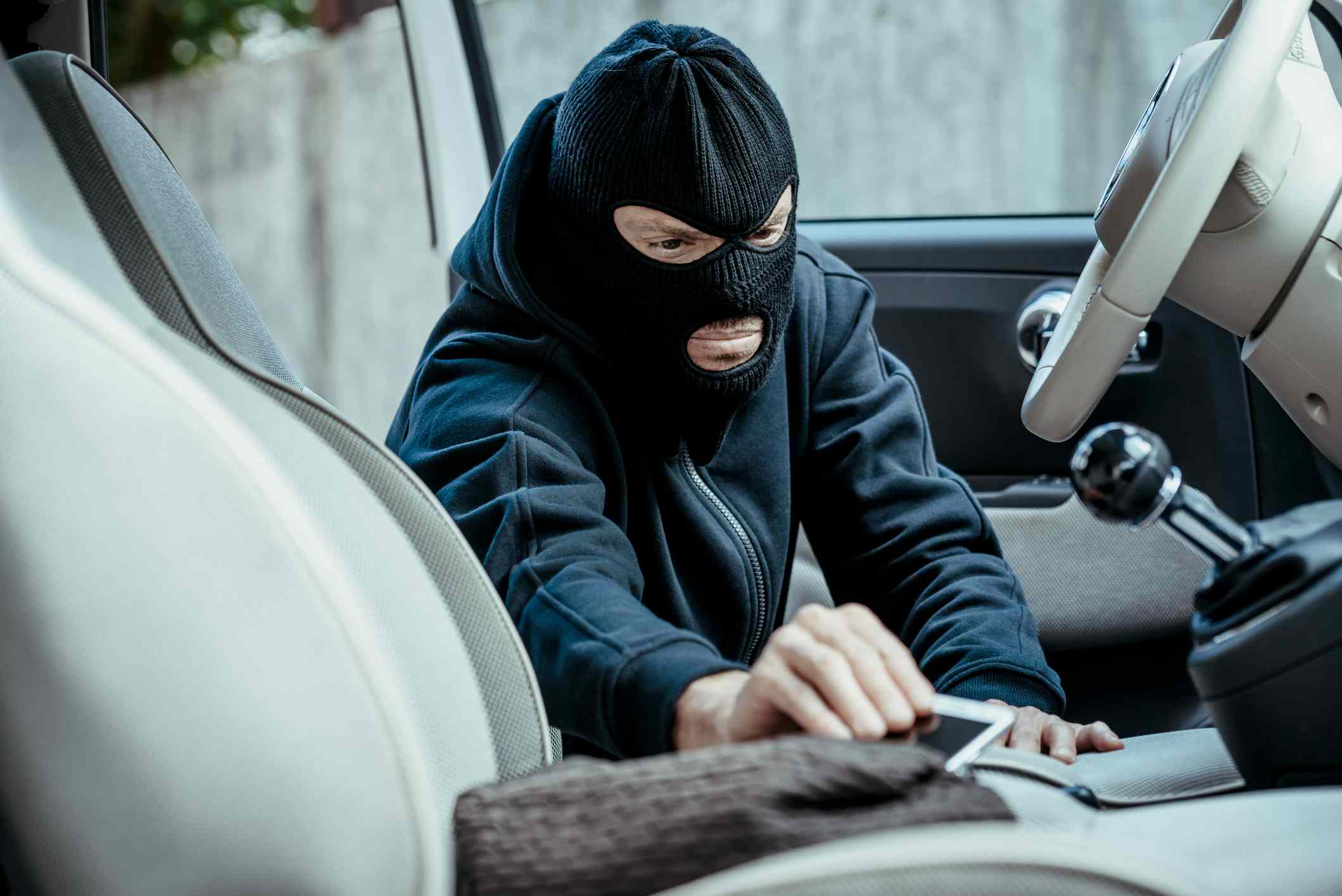 Masked person taking iPhone out of a purse in a car