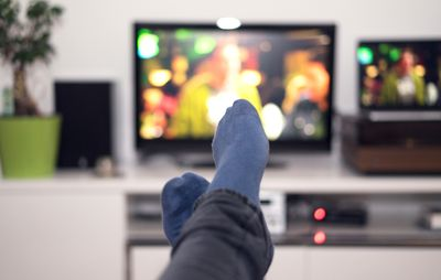 View of a man watching TV with his feet crossed in front of him with blue socks on.