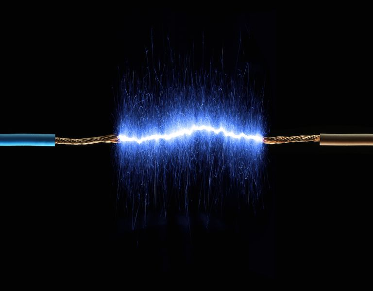 Two copper wires connected by blue sparks against a black background
