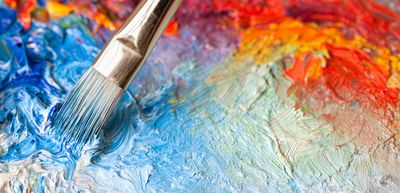Photograph showing a paintbrush painting on a canvas with thick acrylic paints of multiple colors.