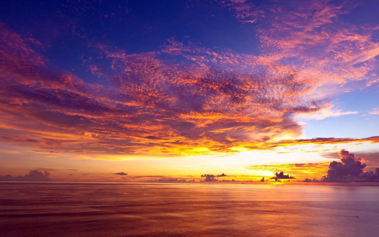 Free ocean wallpaper featuring pink sunset sky and clouds over the ocean