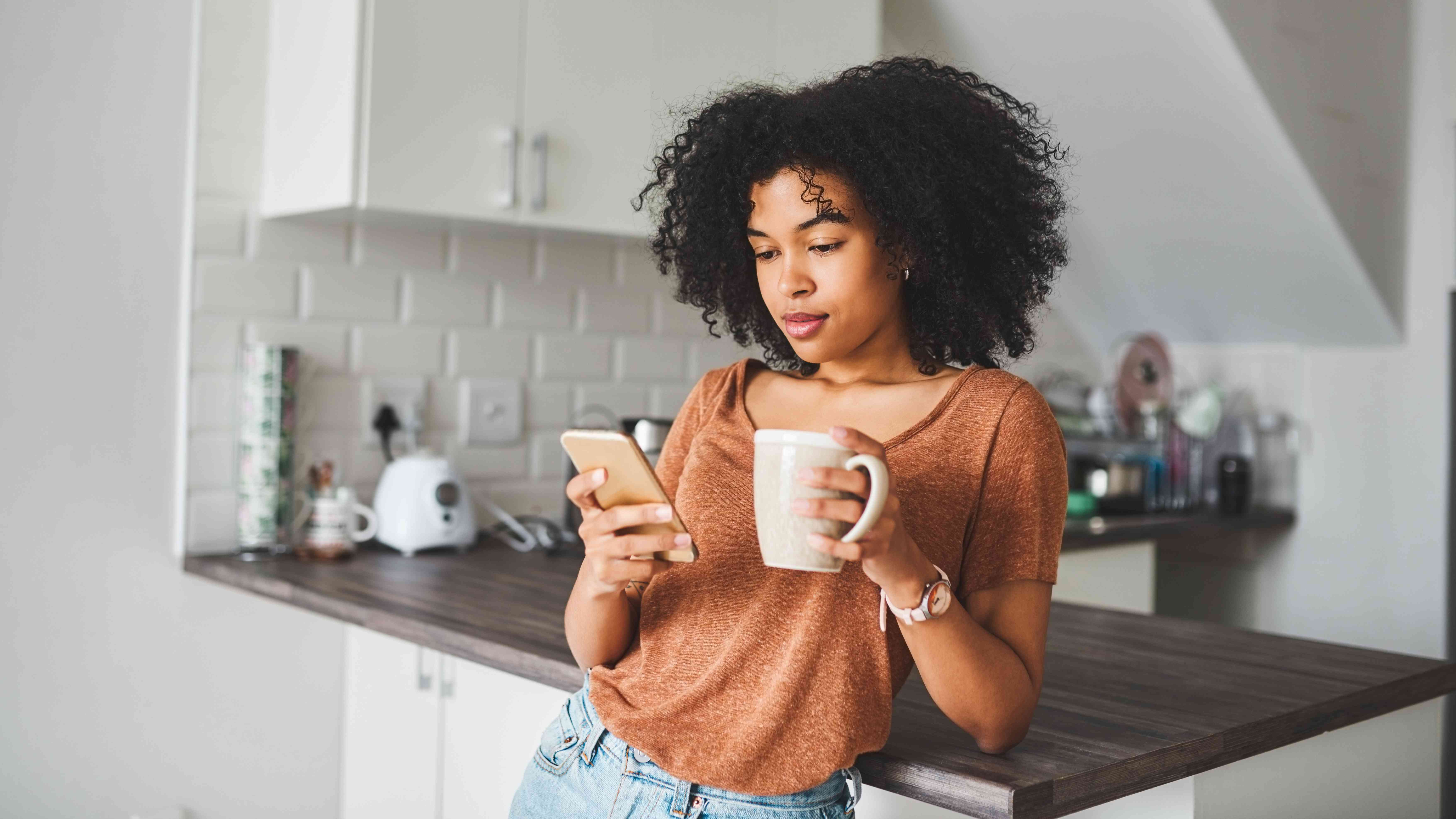 Social media influencer holding a smartphone and coffee while blocking someone on Instagram
