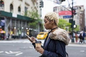 Fashionable woman looking at phone in city