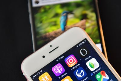 An image of a smartphone showing the Instagram app icon on its screen.