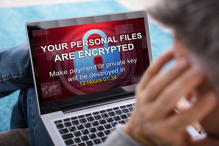 A person looking at a laptop screen displaying a warning message that their files have been encrypted