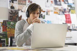 man wearing headphones looking at a laptop