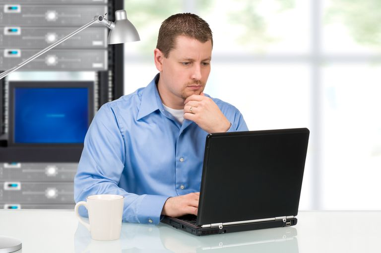 Man working on laptop in front of server rack