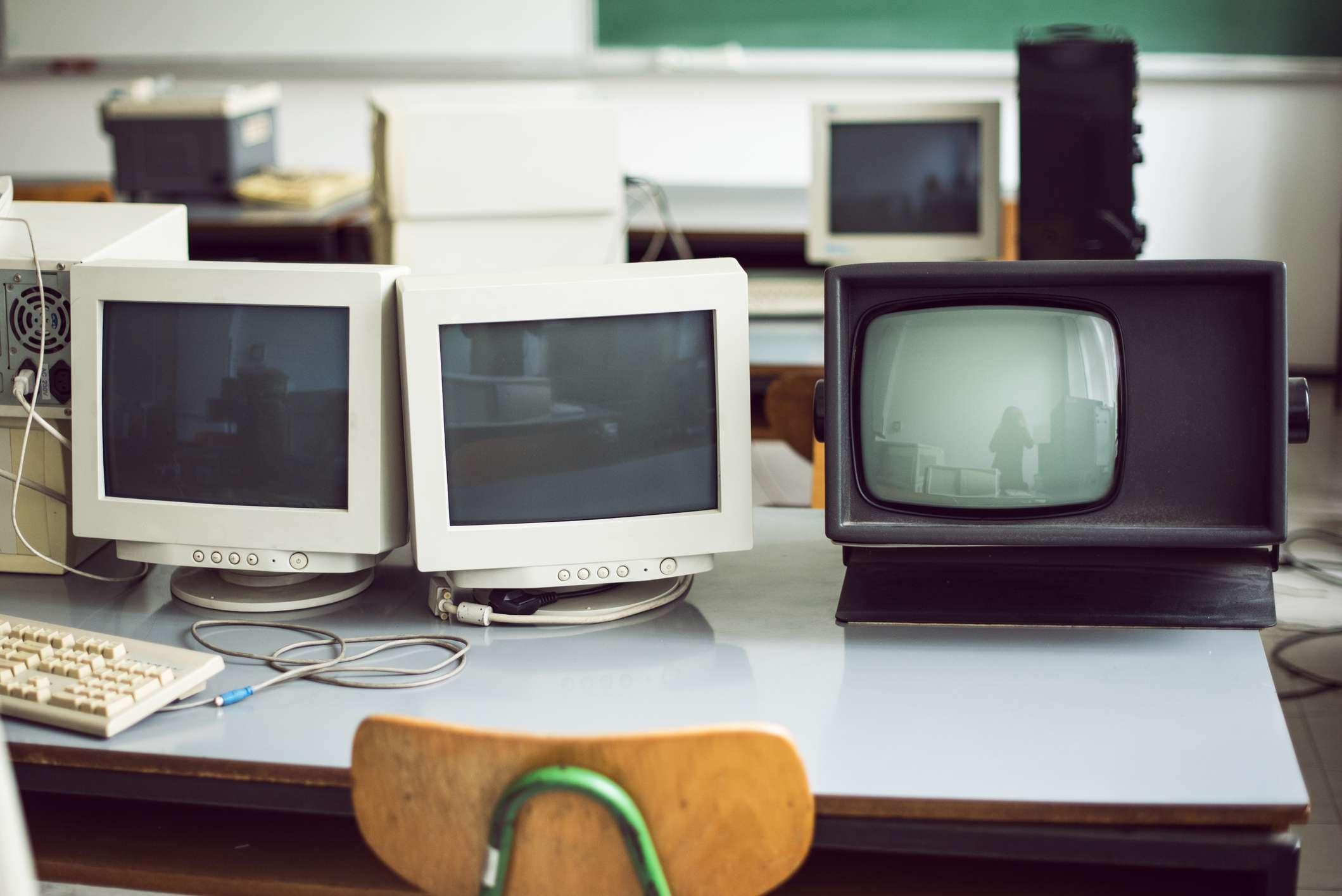 Older CRT monitors on a desk.