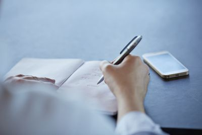 Writing on a notepad with an iPhone near