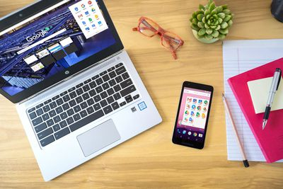 A photo of a chromebook and a smartphone on a desk.