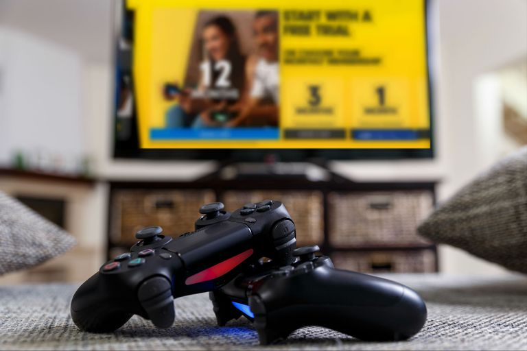 PlayStation 4 controllers stacked in front of a television displaying PlayStation Plus.
