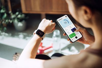 A woman holding her smartphone in one hand while looking at her smartwatch on her other wrist