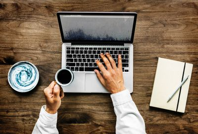 Person browsing internet on laptop with coffee cup in hand