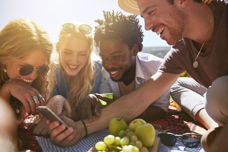A group of smiling friends gathered around one iPhone