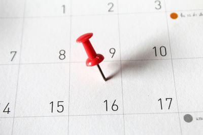 A close-up of thumbtack on calendar.