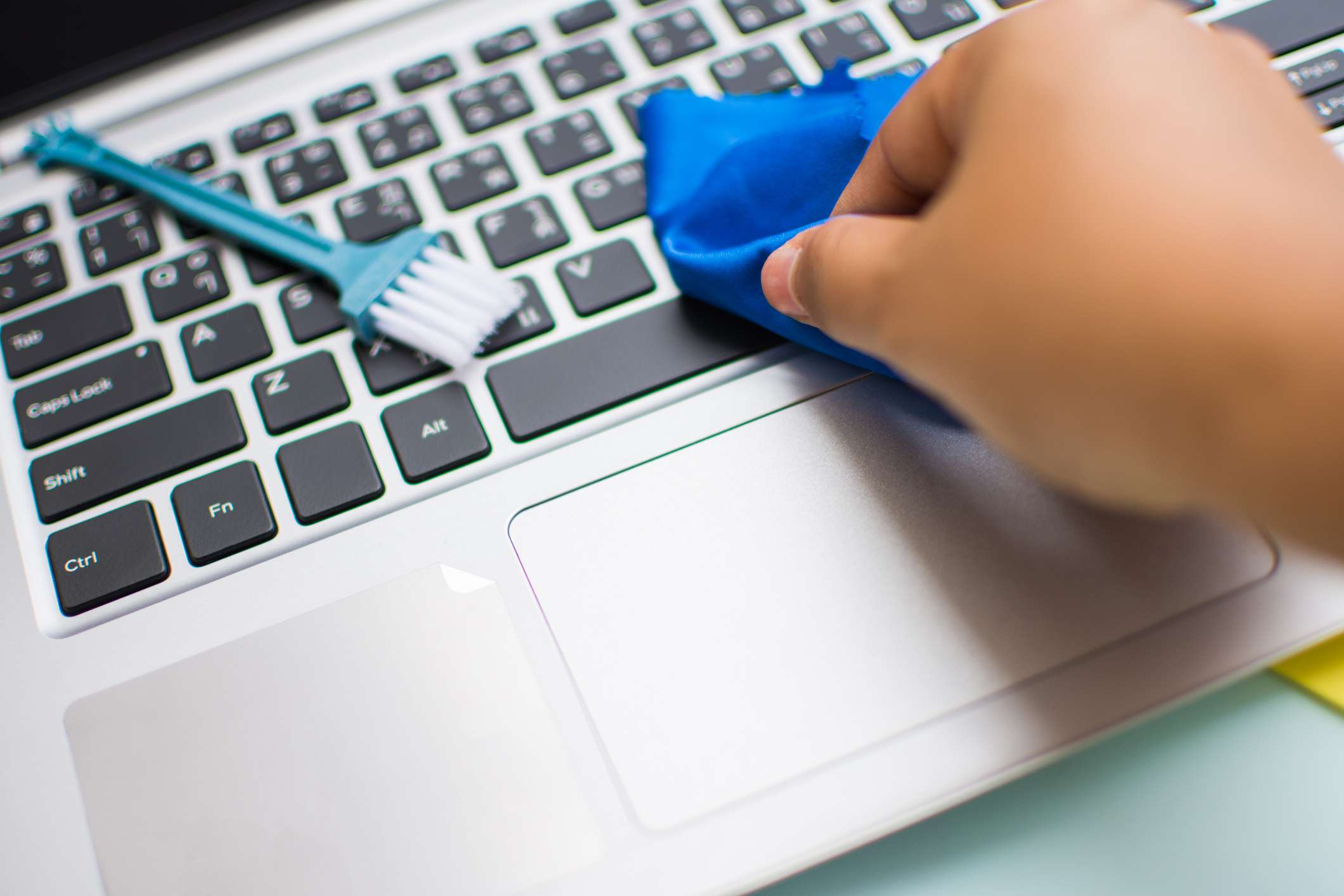 A person wiping a blue cloth over a laptop keyboard with a small brush nearby