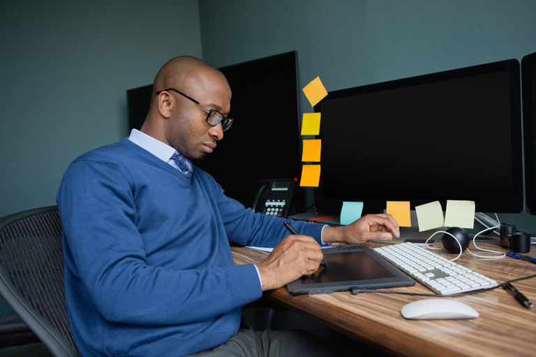 African businessman using graphics tablet at the office