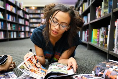 woman laying on the floor or a library or shop reading comics