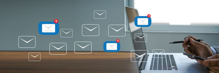 an image depicting multiple email icons behind a laptop screen