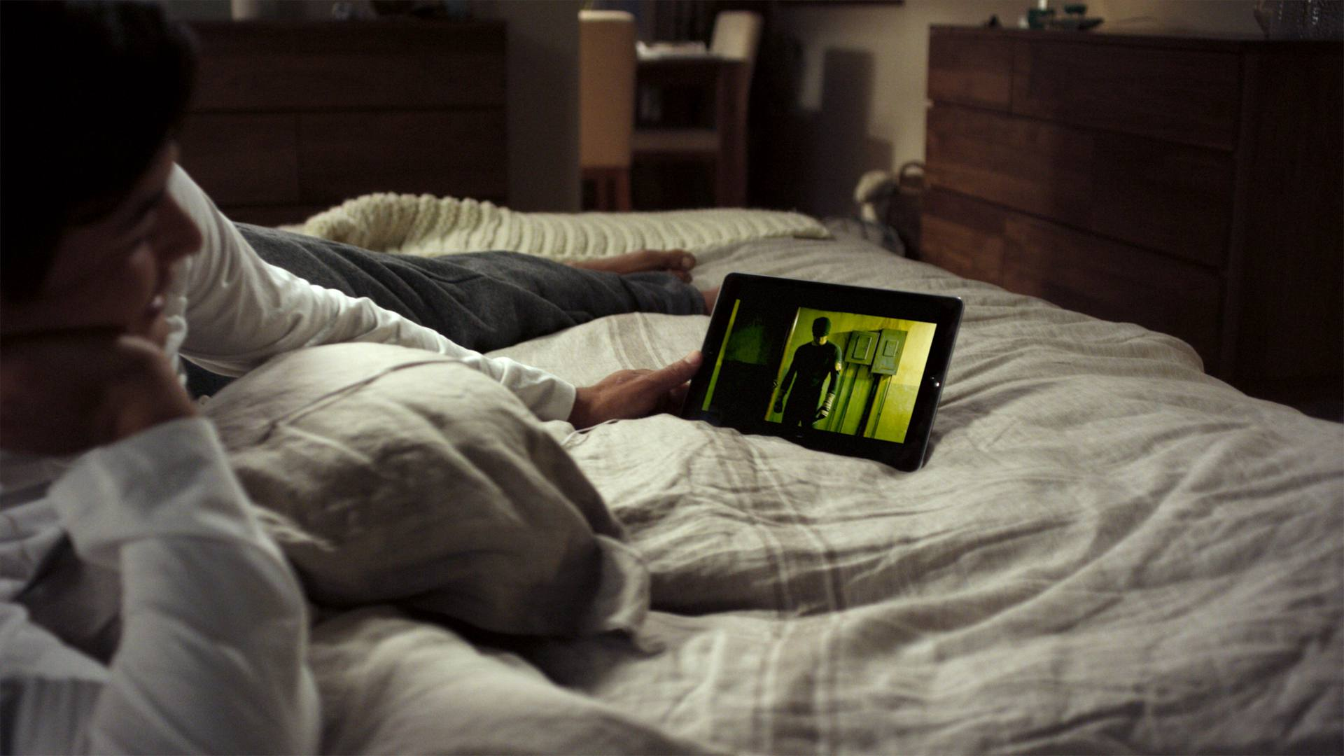 Woman in bed watching Marvel's Daredevil and anime on Netflix on iPad